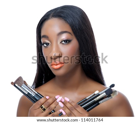 Portrait of an African beauty holding make up brushes