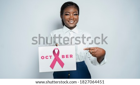 Portrait of an African business woman smiling and holding a sign with pink October - concept on millennial people and breast cancer awareness campaign