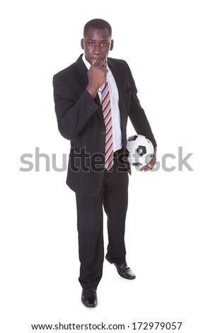 Portrait Of An African Businessman Holding Football Blowing Whistle