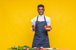 portrait of an african cook holding a plate of tomatoes and a spoon with a smile on his face