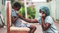portrait of an African nurse or physician in scrubs auscultating chest of a child with a stethoscope outdoors,wearing face mask for protection outdoors,social distancing - desaturated green feel