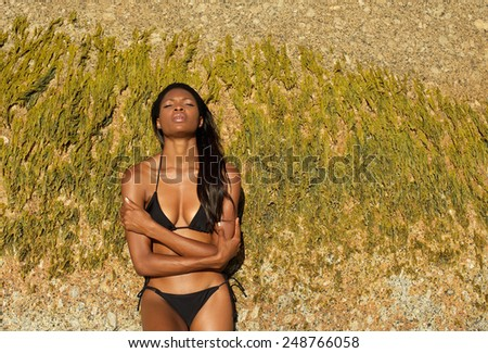 Portrait of an african woman in black bikini with arms crossed