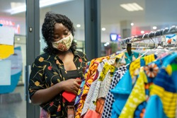 portrait of an African woman wearing homemade mask,touching clothes on hangers - shopping in a boutique in mall in covid-19 pandemic