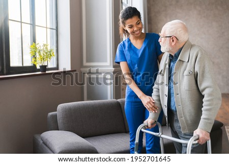 Portrait of an african young nurse helping old elderly disable man grandfather to walk using walker equipment in the bedroom. Senior patient of nursing home moving with walking frame and nurse support