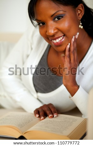 Portrait of an afro-American lady smiling and reading a book while lying on couch at home indoor