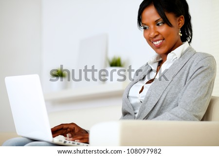 Portrait of an afro-american young girl using laptop at home indoor