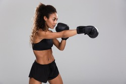 Portrait of an afro american young sportswoman doing boxing isolated over gray background