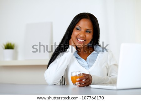 Portrait of an afro-american young woman holding an orange juice glass while thinking in front a laptop