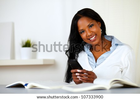 Portrait of an afro-american young woman, smiling and looking to you while is using a cellphone at home indoor