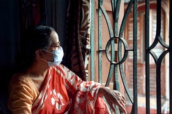 Portrait of an aged Indian (Bengali ethnicity) looking outside from her room window. As precaution from covid-19 pandemic, she is wearing surgical face mask.