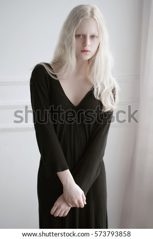 Shutterstock Portrait of an albino girl in black dress behind the white wall