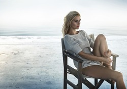 Portrait of an alluring woman sitting on the retro wooden  chair