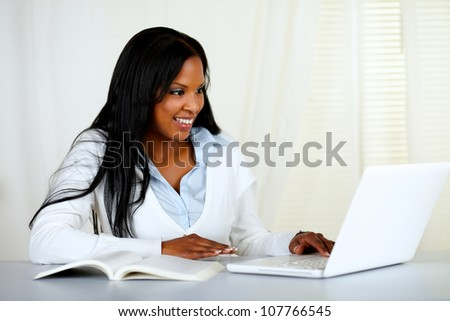 Portrait of an american young black woman working on laptop at home indoor