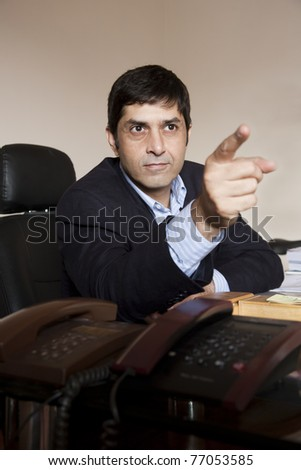 portrait of an angry businessman pointing his finger