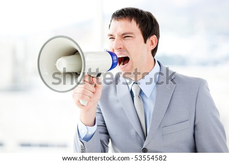 Portrait of an angry businessman using a megaphone in the office