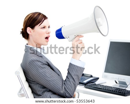 Portrait of an angry businesswoman using a megaphone in the office