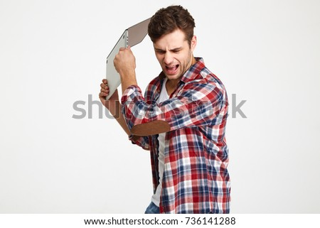 Portrait of an angry furious man throwing his laptop computer isolated over white background