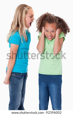 Portrait of an angry girl screaming at her friend against a white background