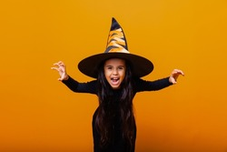Portrait of an angry little girl in a witch costume, on a yellow background. halloween.