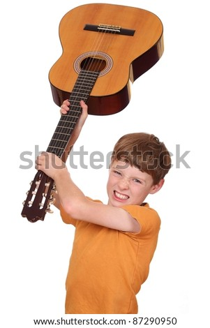 Portrait of an angry young boy with a guitar - stock photo