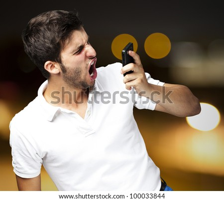 portrait of an angry young man shouting using a mobile against an abstract background