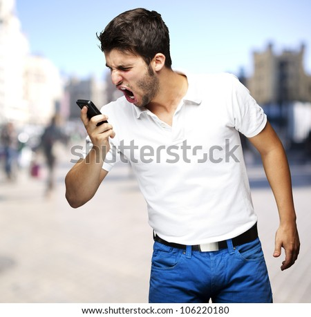 portrait of an angry young man shouting using a mobile at a crowded street