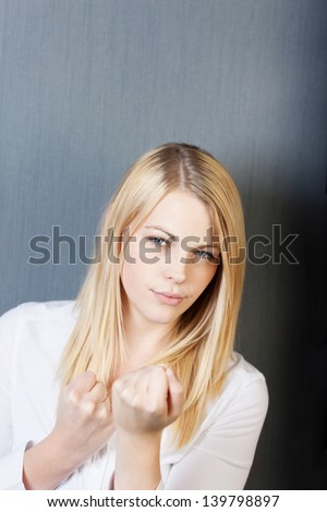 Portrait of an angry young woman with clenched fists isolated over blue background