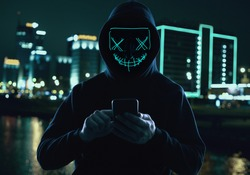 Portrait of an anonymous man in a black hoodie and neon mask hacking into a smartphone. Bright city background