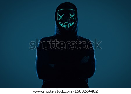 Portrait of an anonymous man in a black hoodie hiding his face behind a scary neon mask. Studio shot. Сток-фото ©