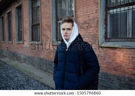 Portrait of an anxious thoughtful sad teenager in hoodie against a brick wall. Concept of problems of adolescents, problems of adolescents and parents #1505796860