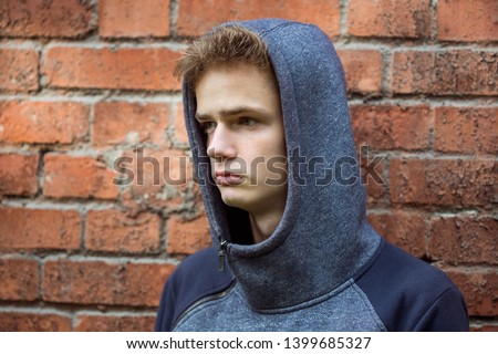 Portrait of an anxious thoughtful teenager in hoodie against a brick wall. Concept of problems of adolescents, problems of adolescents and parents