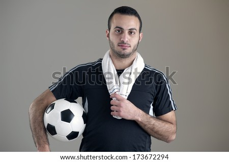 Portrait of an Arab football player holding his ball isolated on grey background