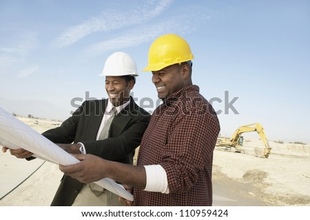 Portrait of an architect and supervisor holding blueprint at construction site