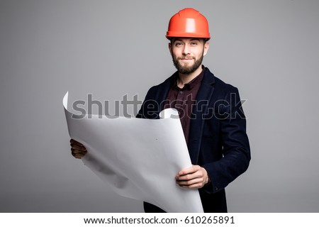 Portrait of an architect builder studying layout plan of the rooms, serious civil engineer working with documents on construction site. #610265891