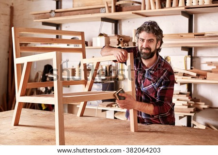 Portrait of an artisan designer, with new piece of furniture, finishing off the sanding of the chair in his studio, with shelves of wood behind him
