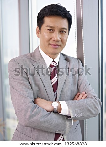 portrait of an asian businessman standing by the windows in office. - stock photo