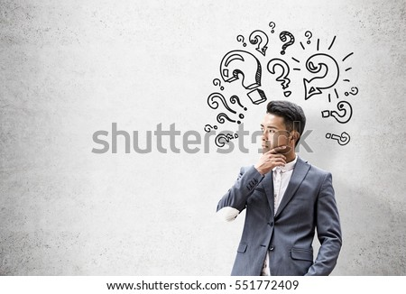Portrait of an Asian businessman who is thinking and solving a problem while standing near a concrete wall with question mark sketches. Mock up #551772409