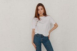 Portrait of an Asian girl in casual wear on a white background. white t-shirt and blue jeans