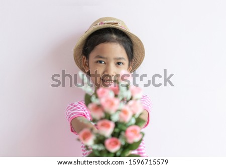 Portrait of an Asian little girl wearing a pink and white striped dress. The child wears a hat and holding rose flowers with smiling and happy. Select the focus and blurred foreground.