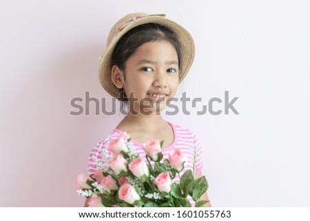 Portrait of an Asian little girl wearing a pink and white striped dress. The child wears a hat and holding roses flowers with smiling and happy.