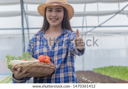 Portrait of an Asian woman holding a basket of fresh vegetables and organic vegetables from the farm. Vegetable cultivation and hydroponics. Health concept for agriculture
