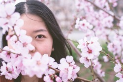 Portrait Of An Asian Woman's Face Partially Hidden By Cherry Blossoms