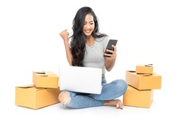 Portrait of an Asian woman sits on the floor with a lot of boxes on the side. She uses a laptop and a smartphone to shop online. Isolated on white background
