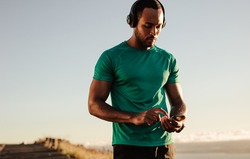 Portrait of an athlete using mobile phone during morning run. Athletic man listening to music on wireless headphones.