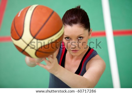 Portrait of an athletic young woman playing basket-ball in a gymnasium