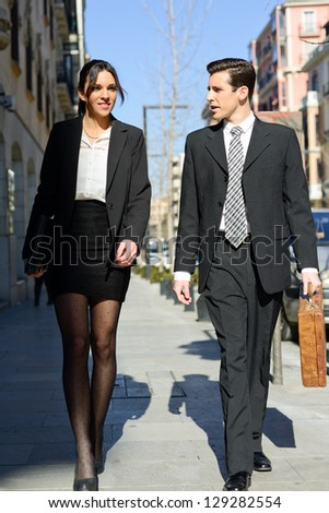 Portrait of an atractive business people walking on the street. Couple working.