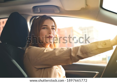 Portrait of an attentive pretty young woman driving a car on a sunny day. Foto stock ©