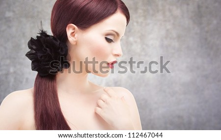 Portrait of an attractive adult woman, concrete wall behind her