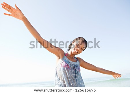 """Portrait of an attractive """"african american"""" woman standing by the sea and smiling with her arms outstretched while on a beach vacation."""