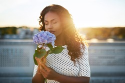 Portrait of an attractiveafroamericanwoman smelling a flower